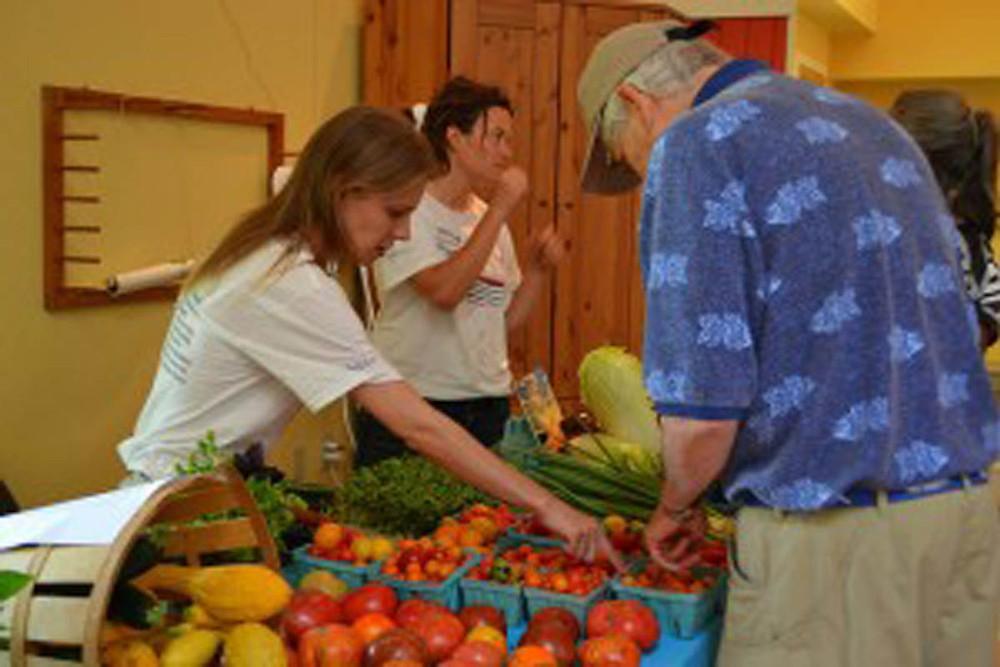 Accokeek Foundation member and market supporter shops organic produce at the Ecosystem Farm Market.