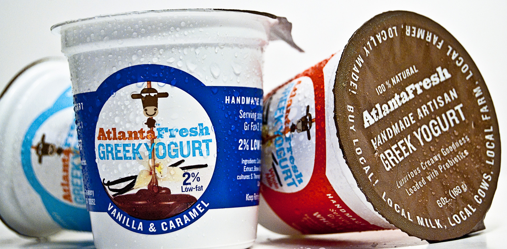 "The original package design of AtlantaFresh used a style that connected with its small batch handmade roots. The label was hand applied and even rubber stamped with the date the batch was made. Therefore much research went into substrates, coatings inks and adhesives to insure the unprecedented yogurt label would hold up in cold and wet conditions. Although the diecut ""cigar band"" signature shape was far more expensive than a flexo printed plastic carton, the client agreed that for such an expensive premium product, an appropriate presentation was needed."