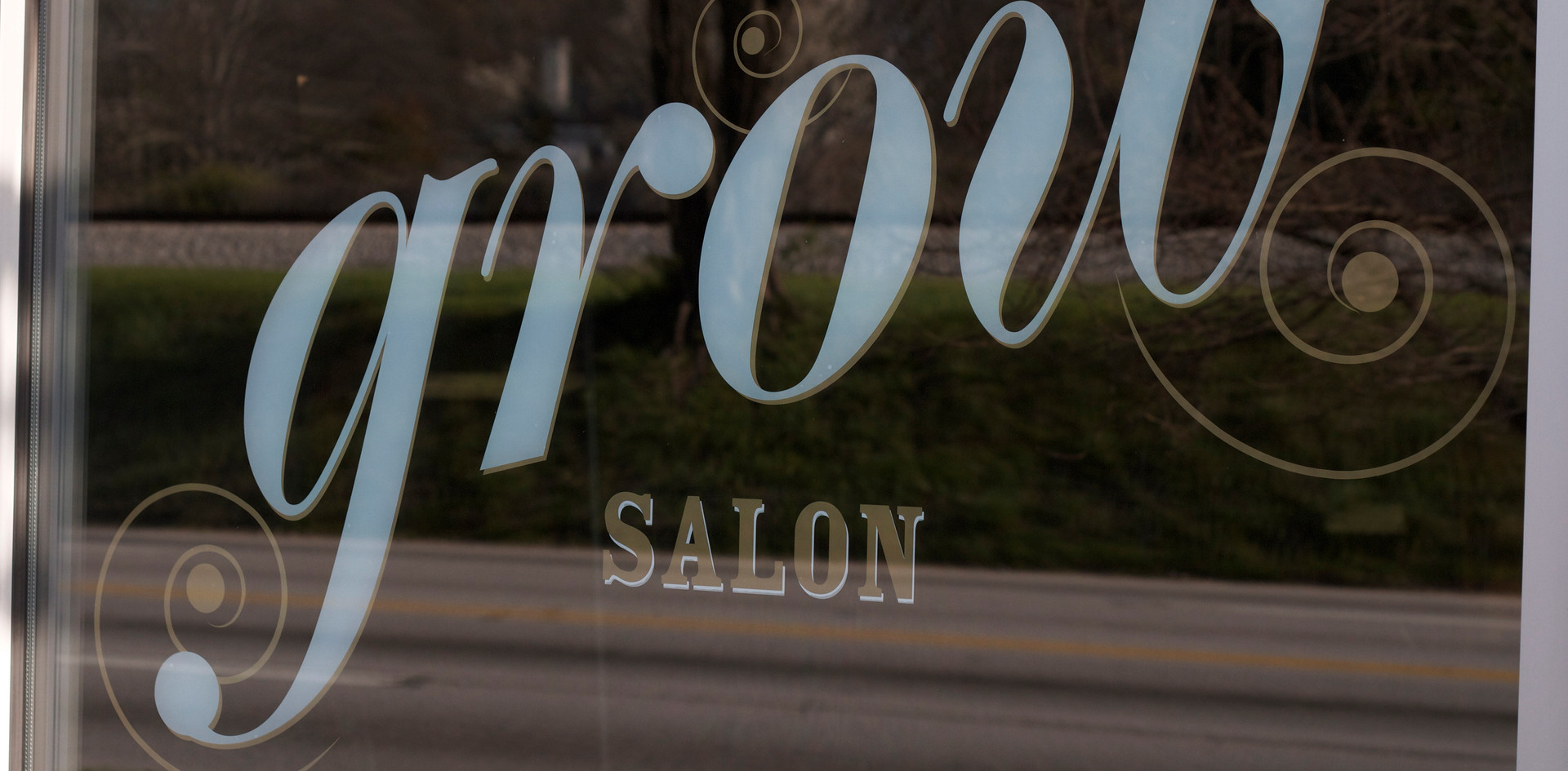 Metallic gold and white window decals evoke classic barber signage.