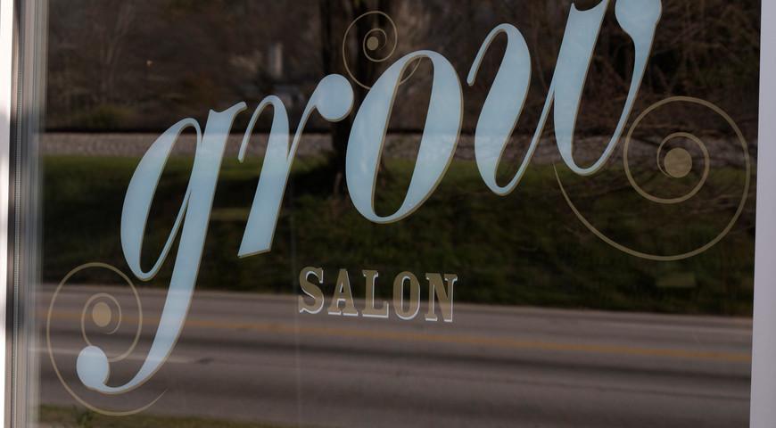 Metallic gold and white window decals evoke classic barber signage.
