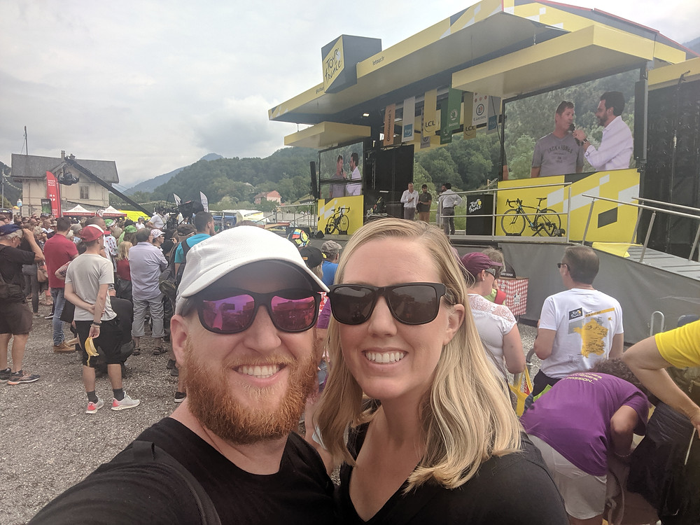 Eddie and Megan standing in front of a yellow stage at the start of stage 20 for Le Tour de France, 2019
