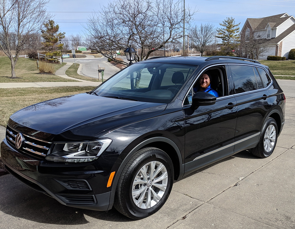 Eddie sitting in the driver seat of a 2018 black VW Tiguan SE