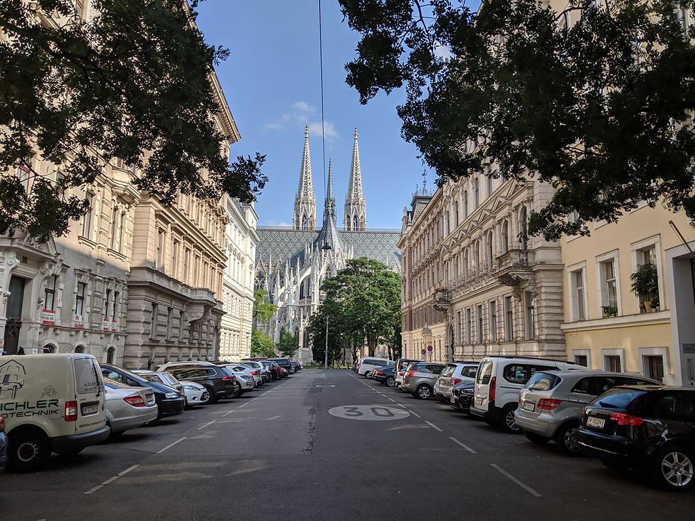 City street in Vienna with beautiful architecture and Votivkirche, a large cathedral
