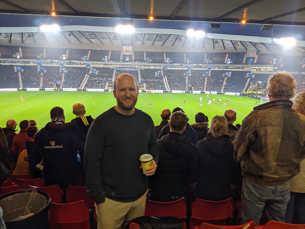 man at a nighttime football match in Scotland
