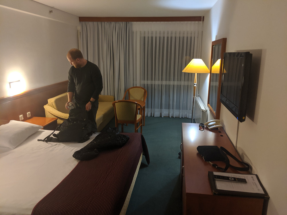 standard hotel room with a single double bed, sofa, table and two chairs, and lamp
