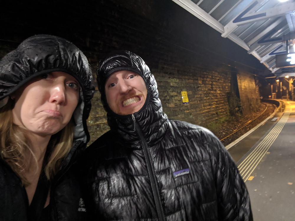 two people wait at a train station after getting soaked in the rain