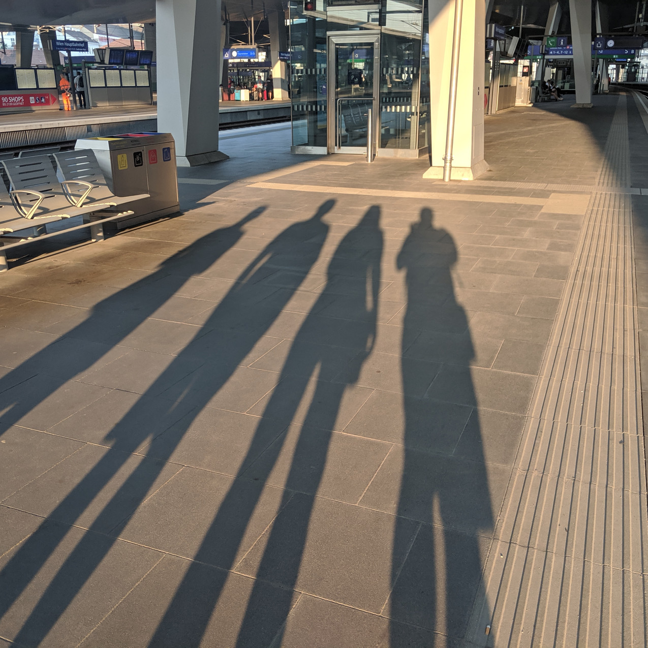 Photo of our four shadows on the sidewalk at a train station.