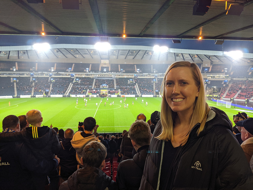 woman at a large football stadium at an evening match