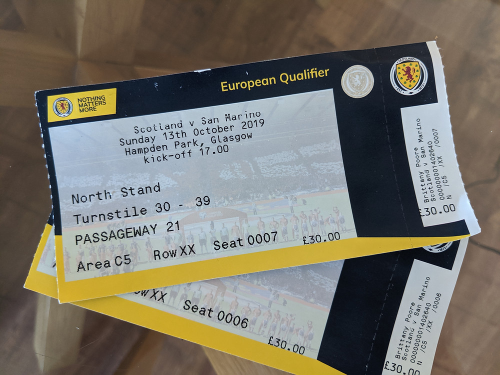 two tickets to a football match sitting on a table