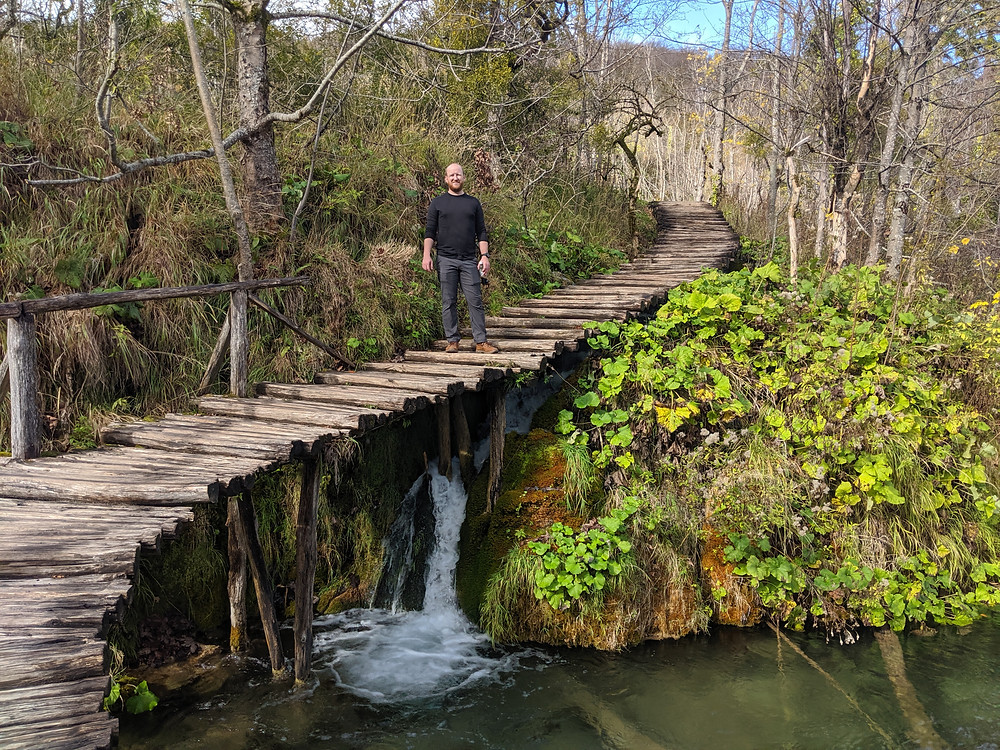 man standing on a boardwalk over a waterfall with lots of greenery surrounding him