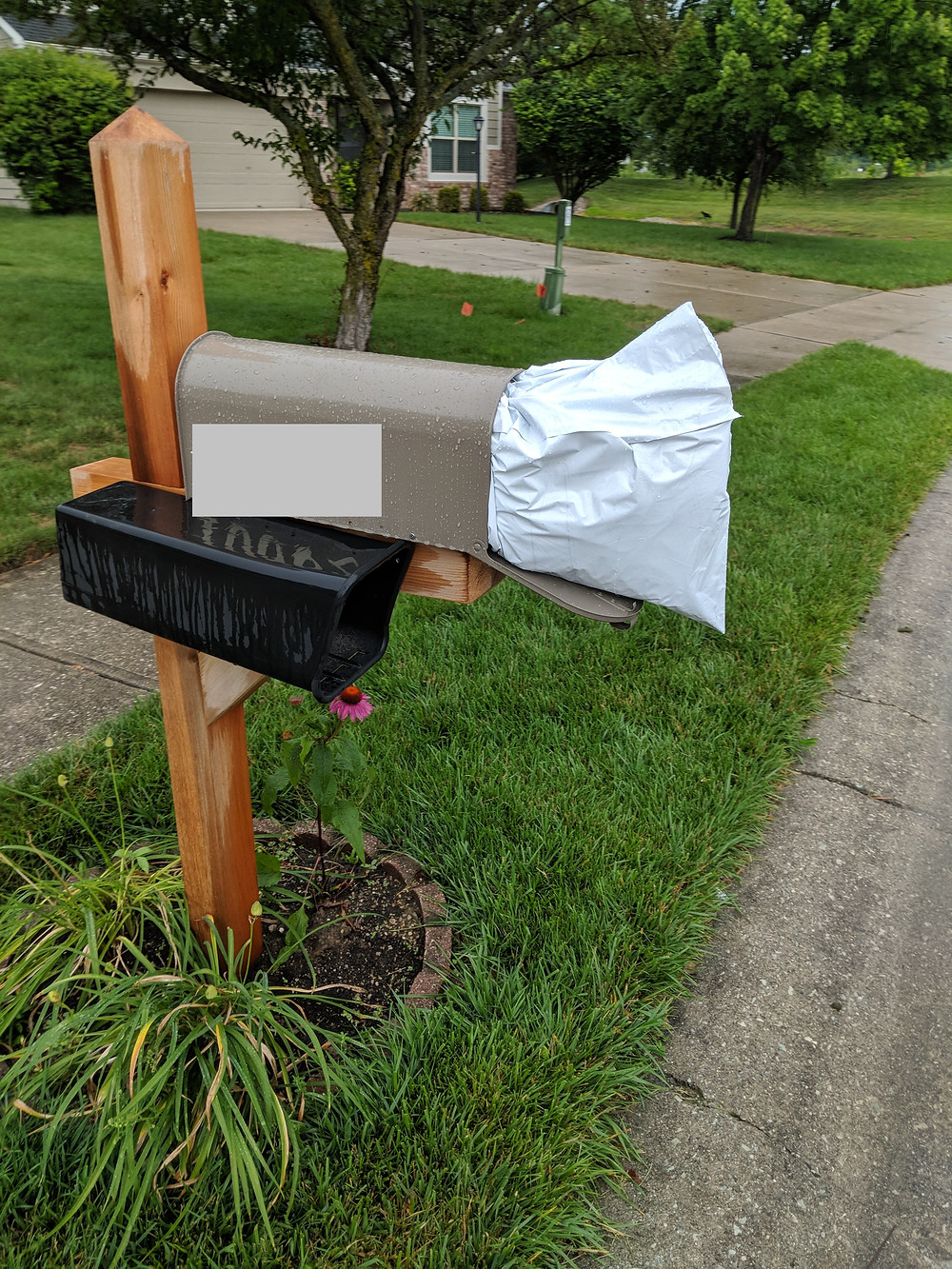 a suburban mailbox and yard with the box full of packages that don't fit