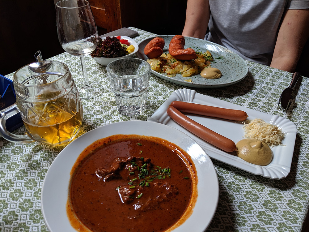 Traditional Viennese goulash (looks like beef stew or chili), a Frankfurter with mustard and shaved horseradish, and a bratwurst on top of a bed of fried potatoes.  A beer and some wine to wash it all down!