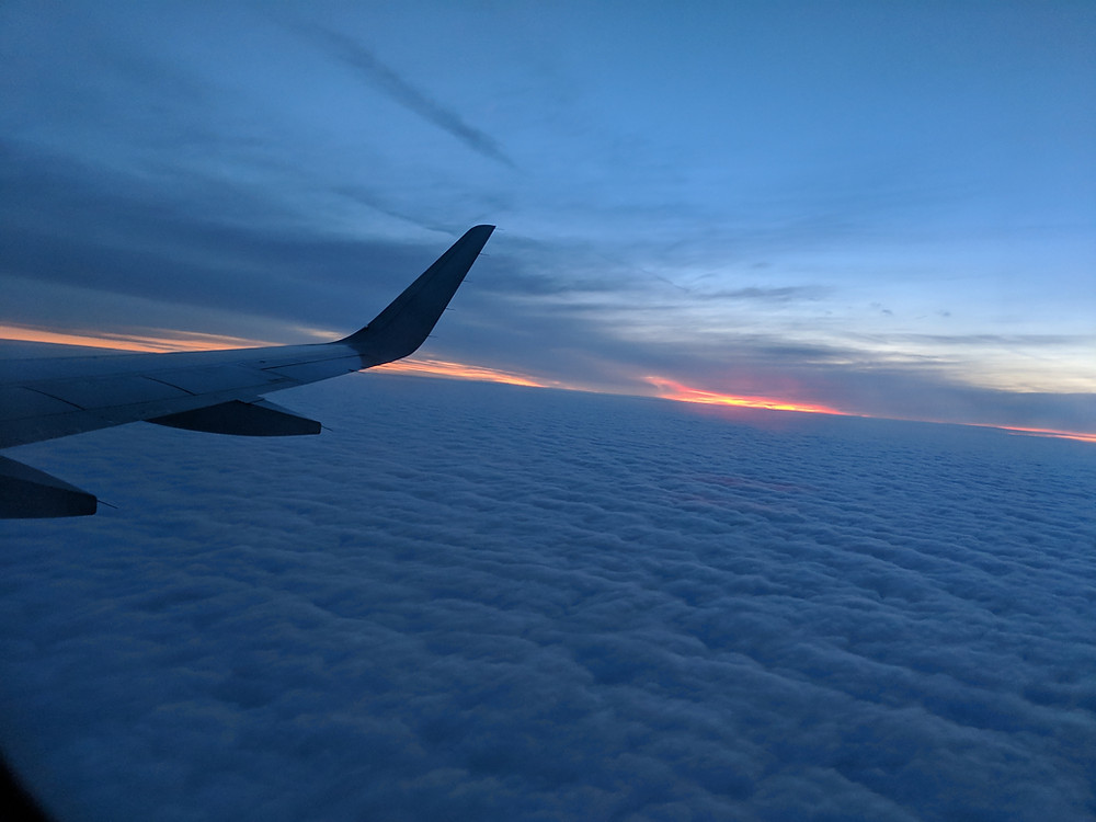 picture of a sunset over the clouds with the wing of the airplane just barely visible