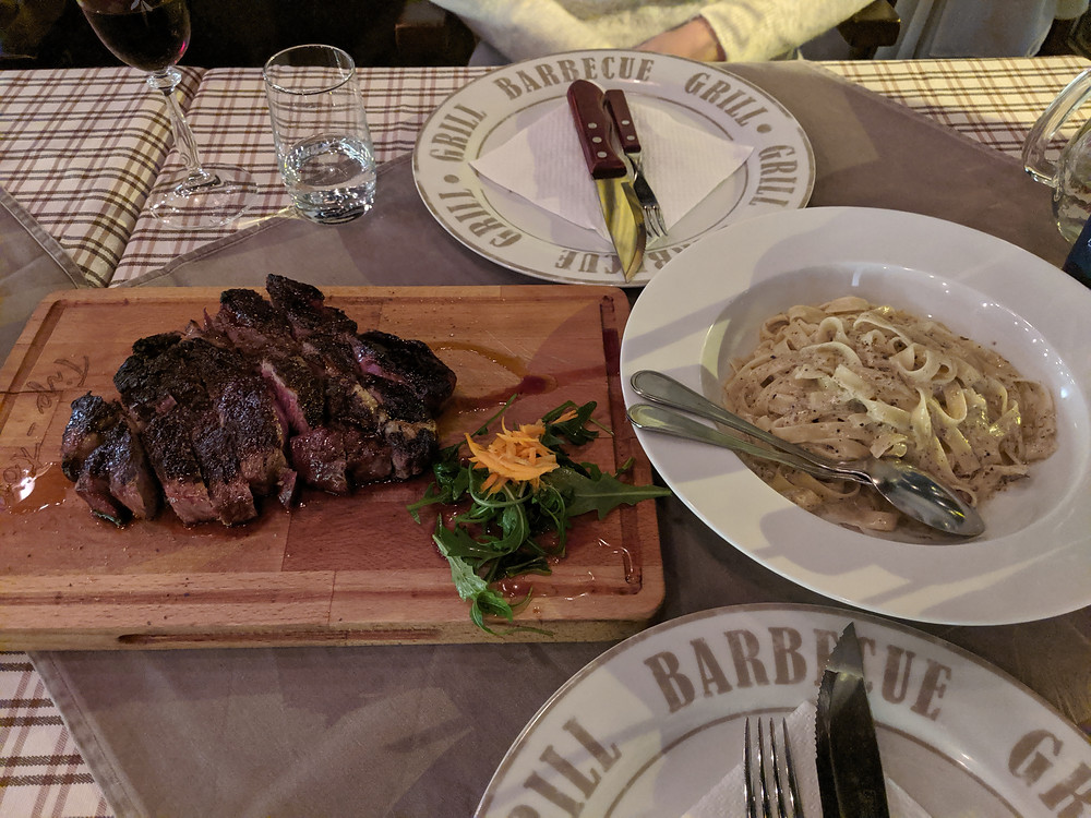 Dining table with steak, pasta, and wine