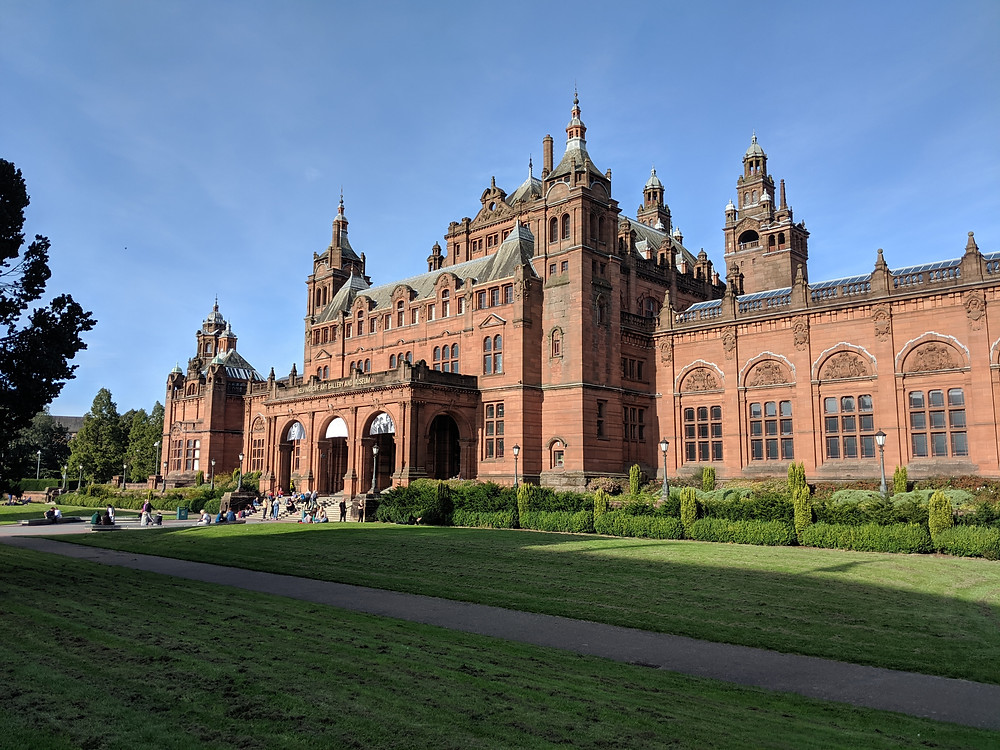 red sandstone building of the Kelvingrove Art Gallery & Museum with perfectly manicured hedges and lawn