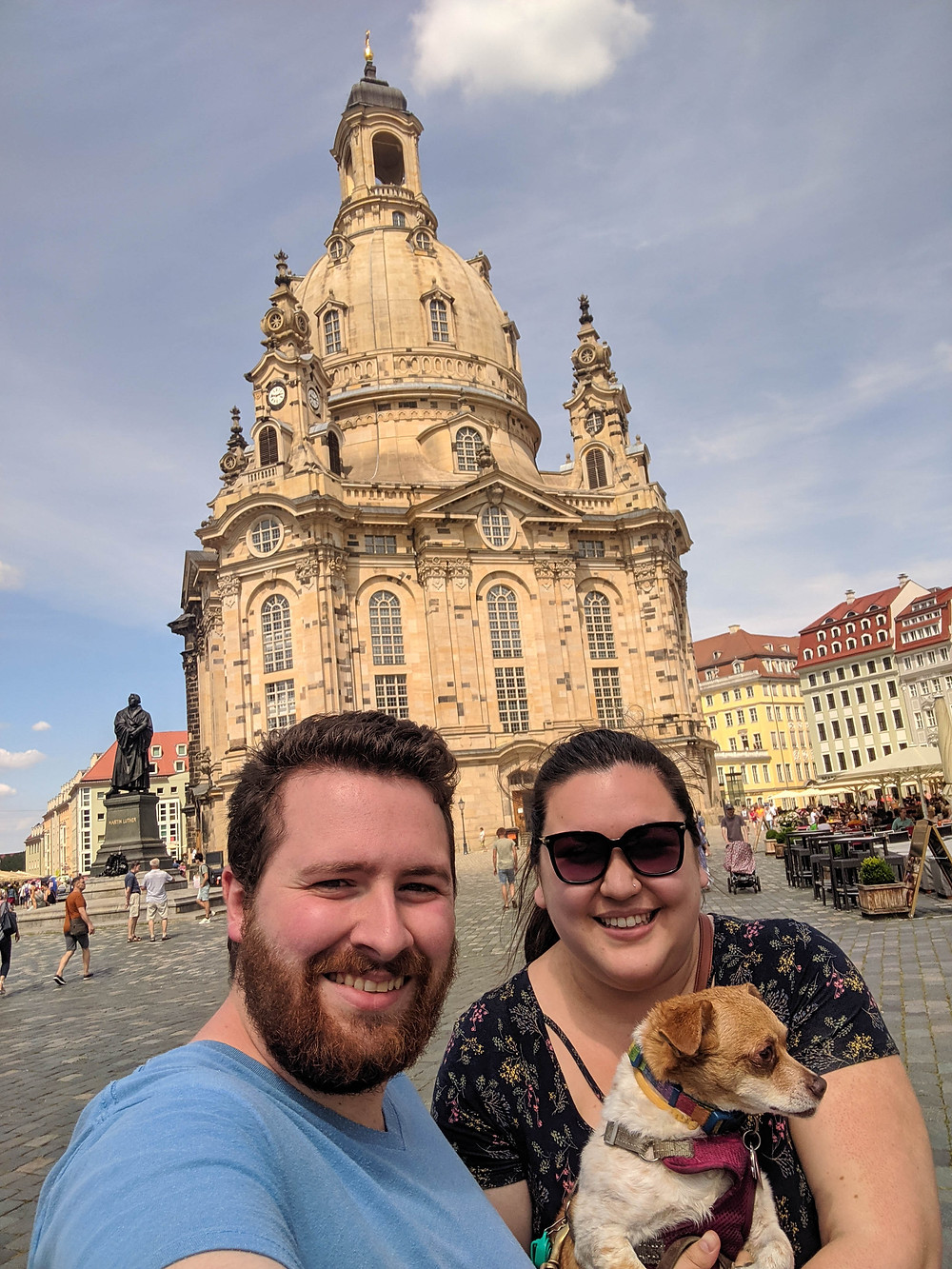 A close up of a young couple and their dog in front of a beautiful cathedral in Germany