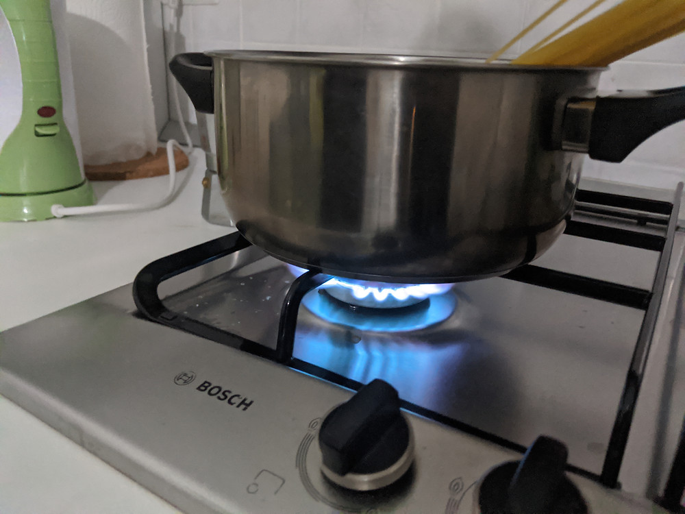 a stove top gas burner with a pot of spaghetti on it