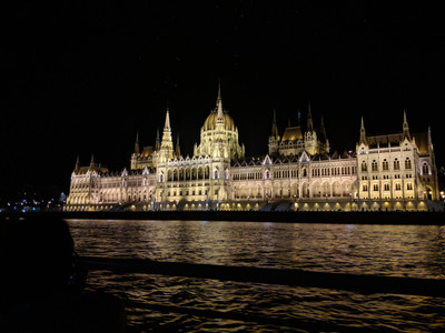 Budapest Parliament building lit up at night from the Danube river.