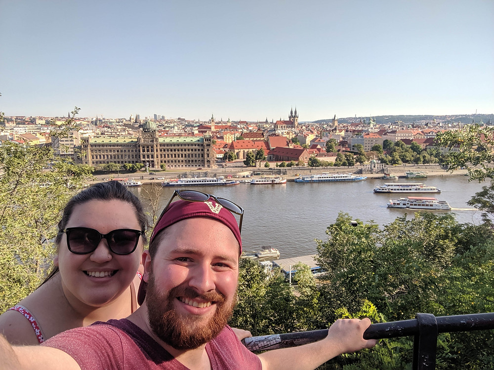 A young couple with a view of Prague behind them