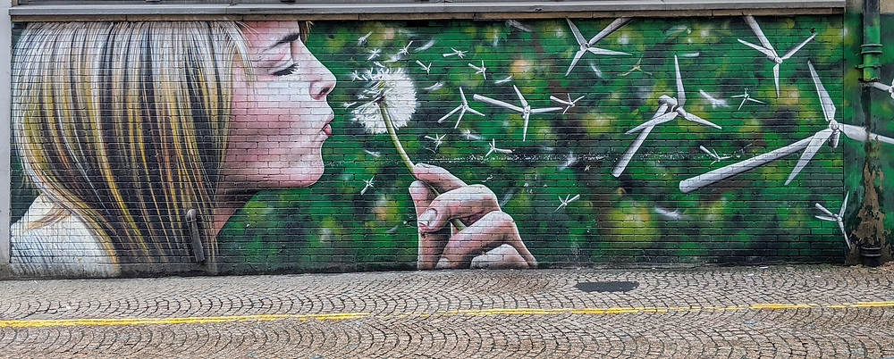 a mural of a young woman blowing the white petals off a dead dandelion
