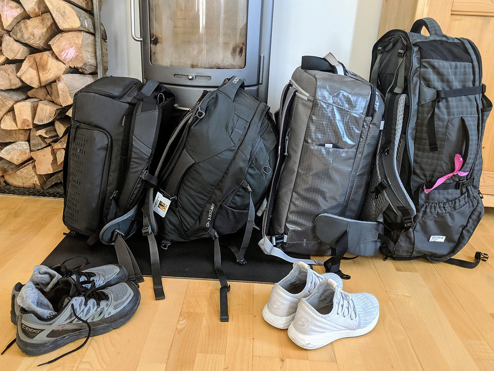 Four large travel packs and two pairs of shoes