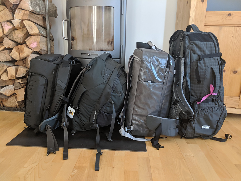 four pieces of luggage lined up in front of a fireplace and stack of wood