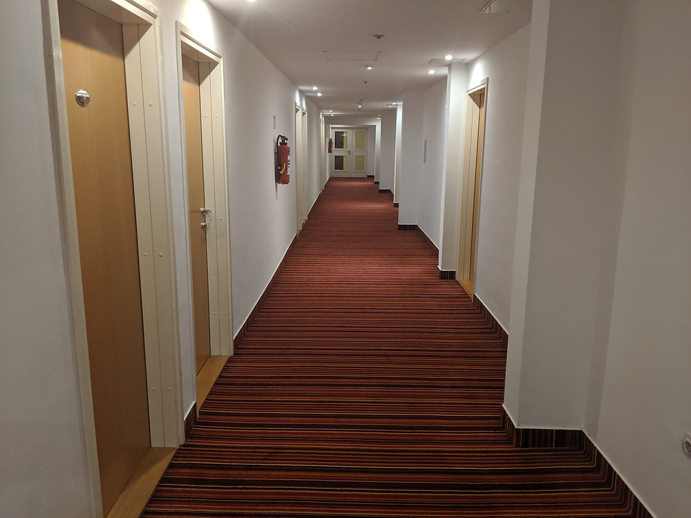 Hotel hallway with red carpet, several hotel room doors, and a fire extinguisher