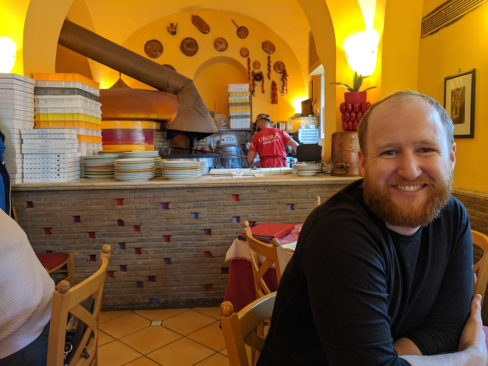 man sitting at a restaurant with the brick oven of a pizzeria in the background