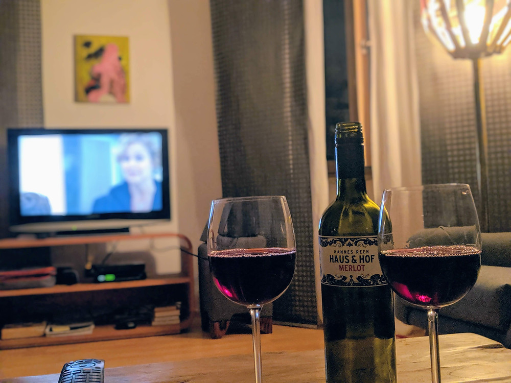 Image of a bottle of wine and two wine glasses on a coffee table and a TV show on in the background.
