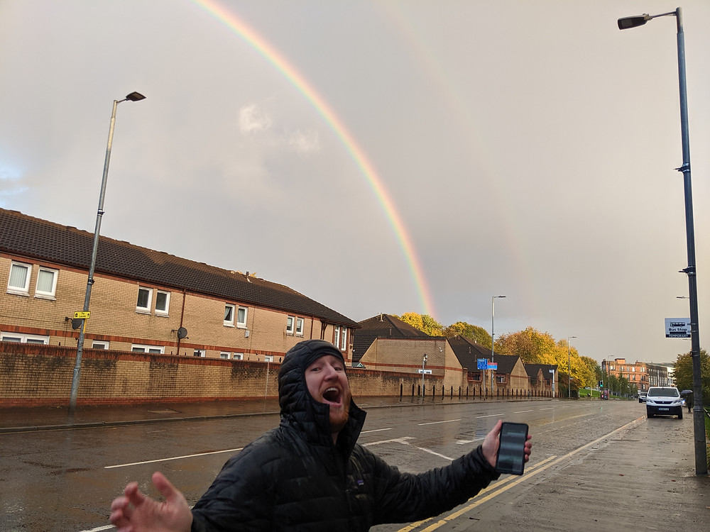 Eddie jumping in front of a rainbow.