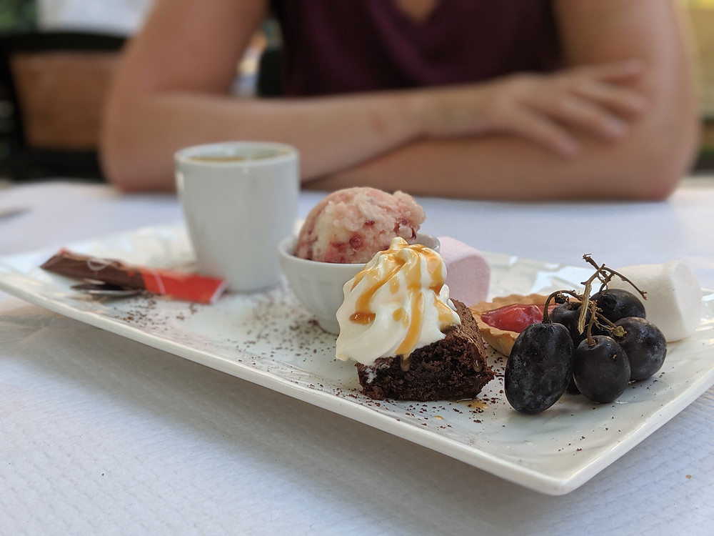 Cafe gourmand. Espresso and a plate of three tiny deserts. Ice cream, brownie, and cherry tart