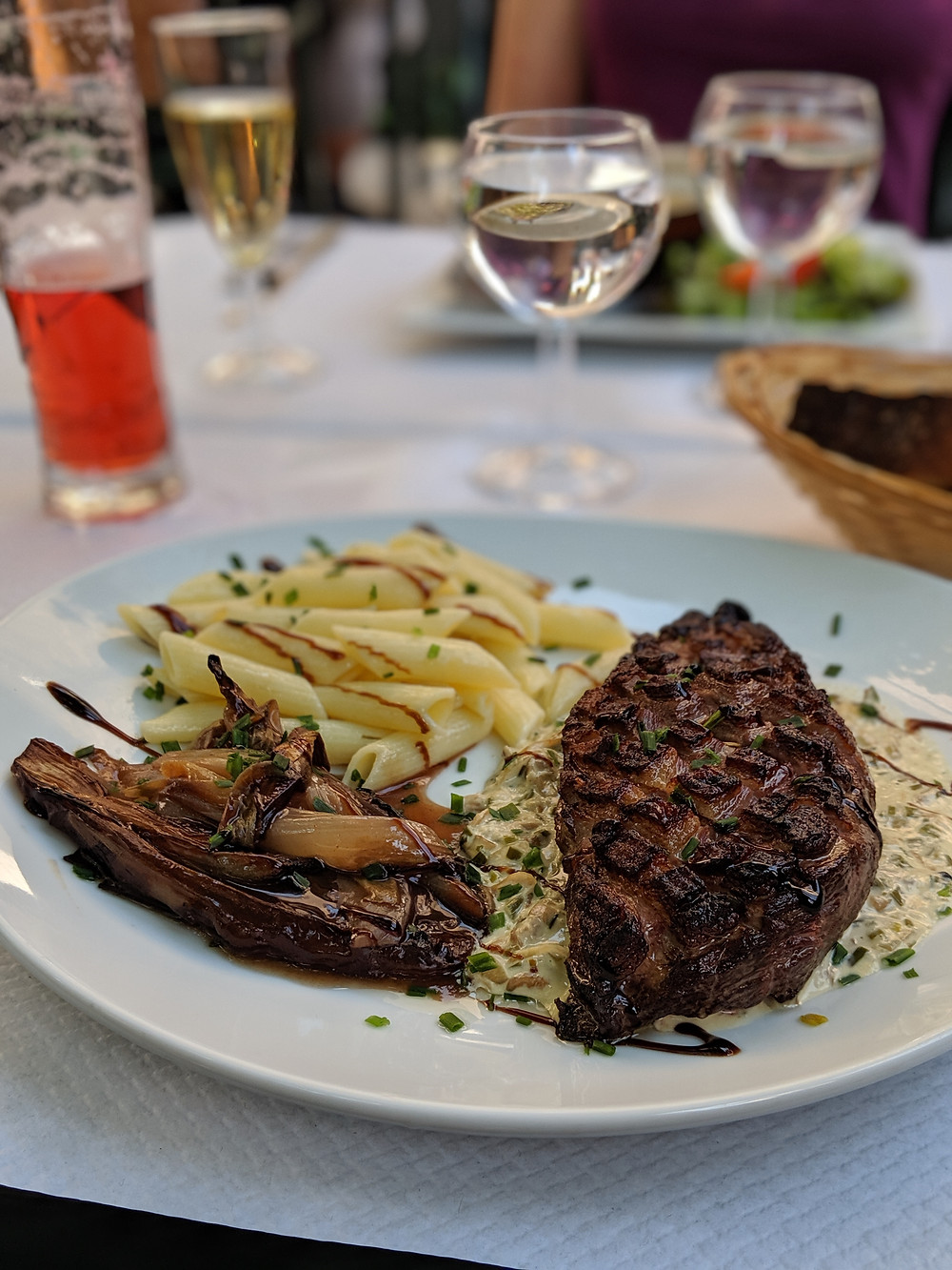 Close up shot of grilled duck on a bed of creamy mushrooms with a side of pasta and grilled endives.
