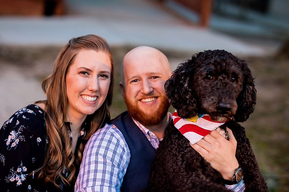 picture of a young couple dressed nicely and their dog with curly black hair