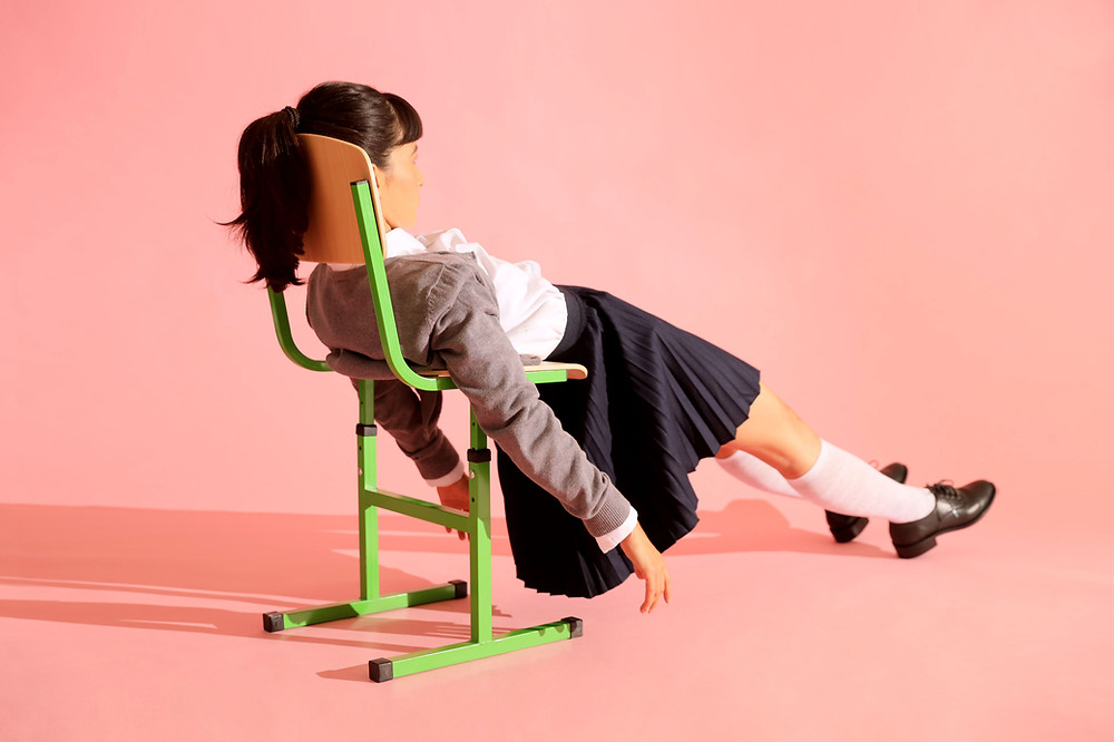 Side view of young woman with ponytail flopped in green school chair, arms and legs outstretched. Pink background.