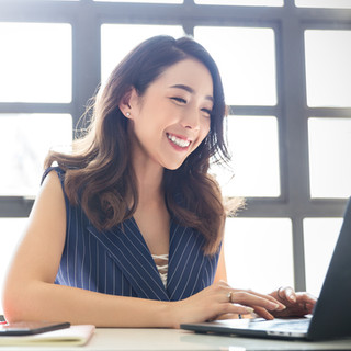 Smiling Person Typing On Laptop