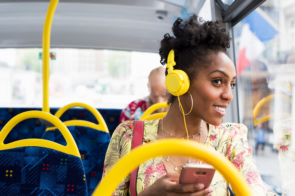 Black woman on bus listening to music on yellow headphones and smiling