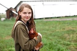 鶏を運ぶ少女
