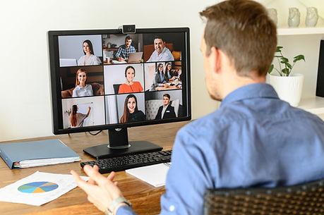 Man sat infont of computer during a video call with work colleagues