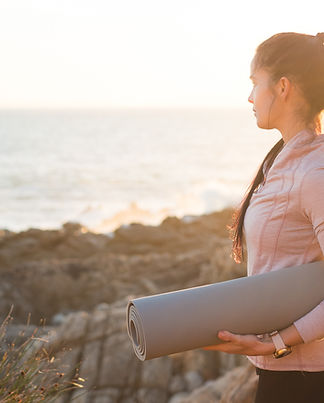Woman holding yoga mat looking out at sunrise
