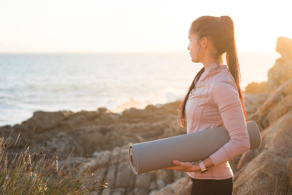 girl near the beach with yoga mat