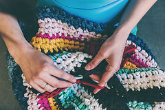 hands holding crochet hook and a colorful striped blanket in lap