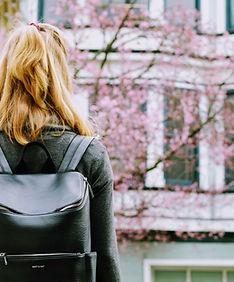 革のバックパックを持つ少女