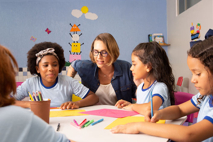 [Image description: A photo of a teacher giving instruction to three students.]