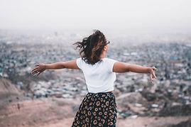 Femme de dos les bras ouverts face à un paysage. Elle semble libre, ouverte et vivante. Elle semble avoi trouvé l'équilibe et l'harmonie.
