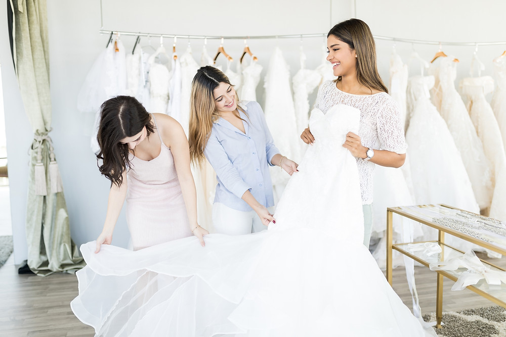 Bride shopping for gown with friends and consultant