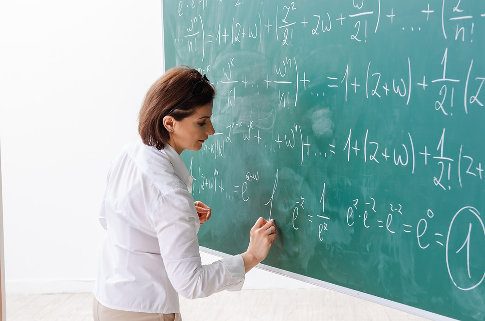 A female maths teacher writing on the board