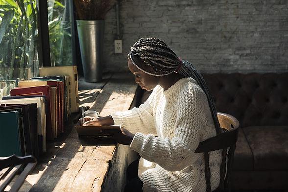Uma mulher escrevendo perto da janela