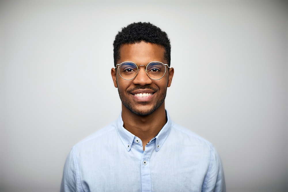 There is a young Black man against a white background. He has short dark hair, and he's hearing glasses and a light blue shirt.