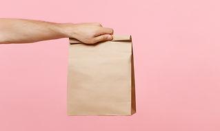 Hand met bruine papieren zak