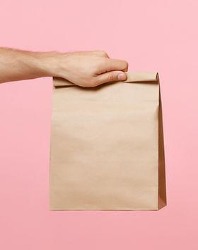 Main tenant un sac en papier brun